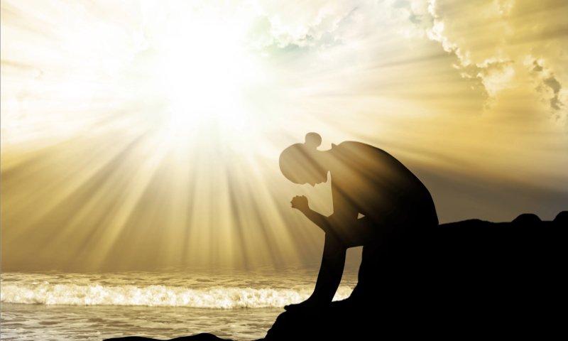 person praying during sunrise