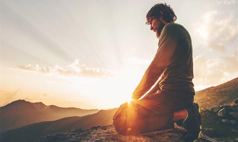 man kneeling during sunrise